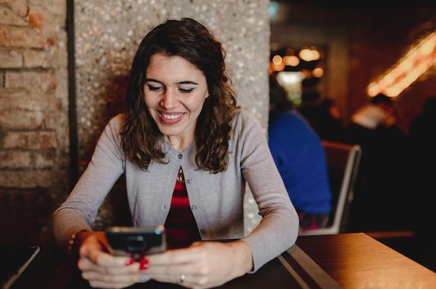 Улыбающийся кавказский портрет молодой женщины в ресторане, держащем и использующем смартфон.