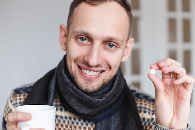 Smiling caught a cold man shows pills for health before taking