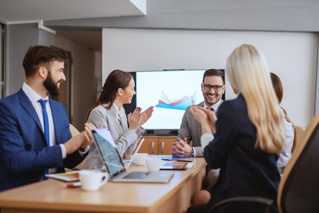 Smiling ceo sitting in boardroom with his team. team clapping to him. a meeting is an event at which the minutes are kept and the hours are lost.