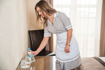 Smiling chambermaid placing the water bottle on table in the hotel room