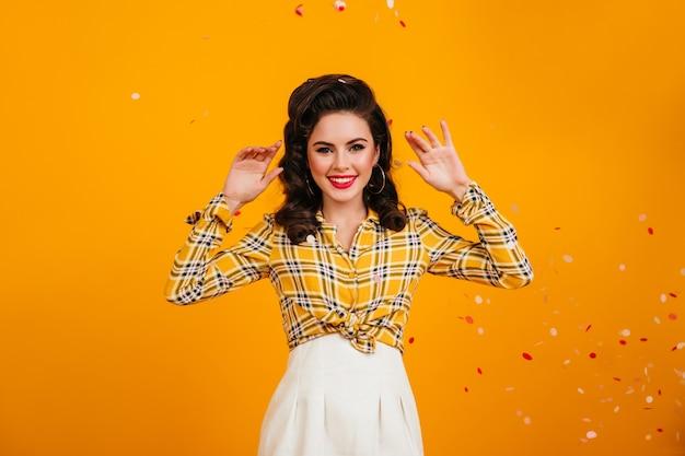 Sorridente donna carismatica in posa con le mani in alto su sfondo giallo. ragazza pinup con acconciatura ondulata che guarda l'obbiettivo.