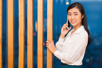 Smiling Charming Asian Lady Calling on Phone