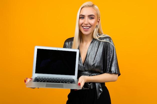 노란색 벽 공간에 빈 노트북 화면을 들고 웃는 매력적인 금발 소녀