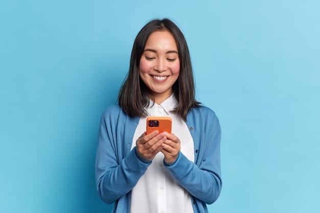 웃는 매력적인 갈색 머리 아시아 여자는 현대 기술에 중독 된 소셜 네트워크에서 휴대 전화 행복 문자 메시지를 사용 캐주얼 점퍼를 착용
