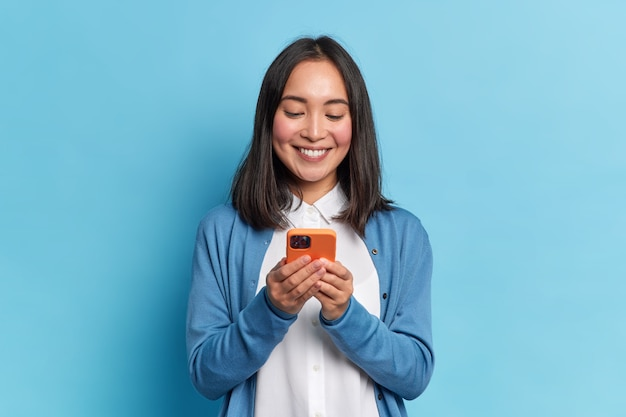 Smiling charming brunette asian woman uses mobile phone happy texting in social networks addicted to modern technologies wears casual jumper