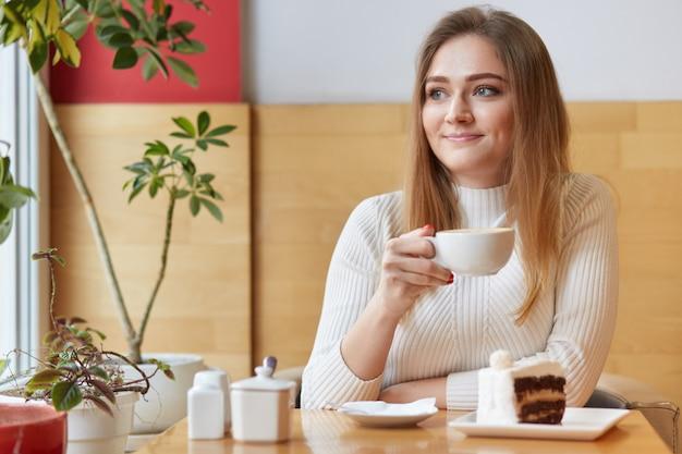 魅力的な女性の笑顔は、白い小さなカップのホットドリンクを片手に、窓の外に見え、屋内では快適に感じ、夢のようで優しく見えます。