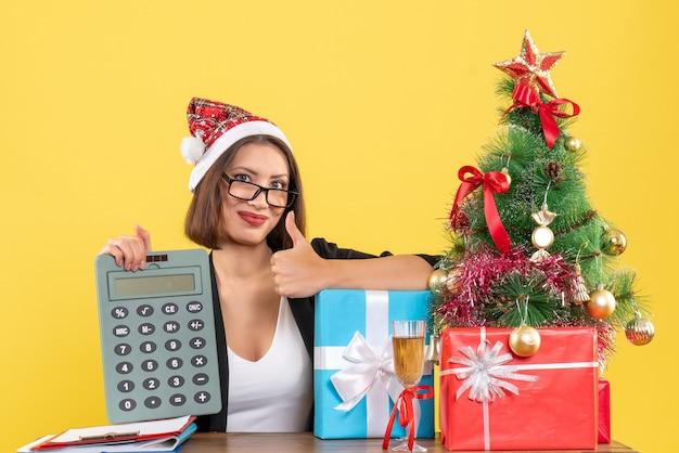 고립 된 노란색에 사무실에서 확인 제스처를 만드는 계산기를 보여주는 산타 클로스 모자와 소송에서 매력적인 아가씨 미소