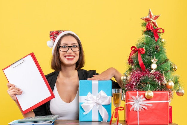 Smiling charming lady in suit with santa claus hat and eyeglasses holding documents pointing gift in the office on yellow isolated