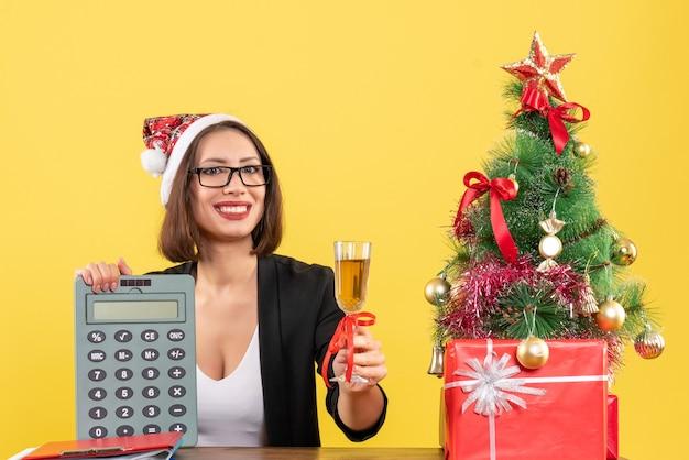 Affascinante signora sorridente in vestito con cappello di babbo natale e occhiali da vista mostrando calcolatrice e alzando il vino in ufficio su giallo isolato
