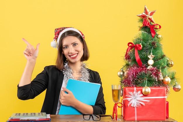 Affascinante signora sorridente in vestito con cappello di babbo natale e decorazioni di capodanno che tengono documento in ufficio su giallo isolato