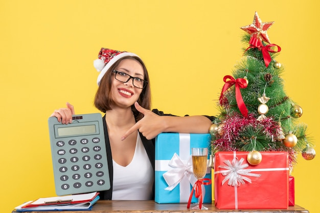 Sorridente affascinante signora in tuta con cappello di babbo natale che indica la calcolatrice in ufficio su giallo isolato