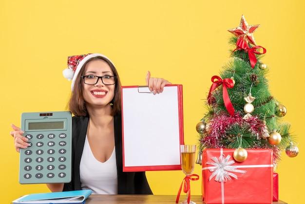 Affascinante signora sorridente in vestito con il cappello di babbo natale che mostra il documento e che tiene il calcolatore nell'ufficio su giallo isolato