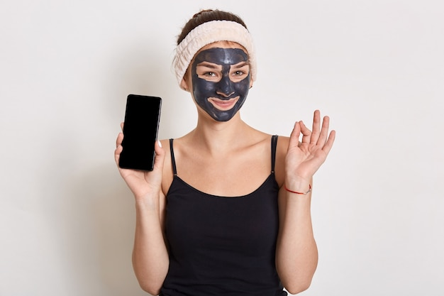 Smiling charming woman wearing hair band and t shirt, holding phone with blank screen, showing ok sing wit fingers