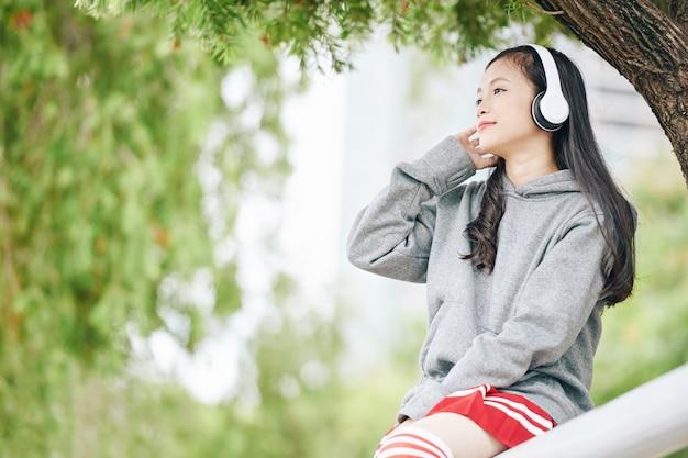 公園で時間を過ごし、ヘッドフォンで音楽を聴いて魅力的な若いベトナムの女の子の笑顔