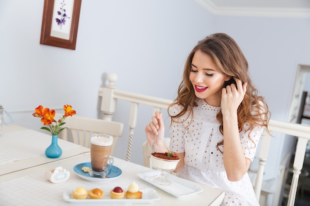 Smiling charming young woman eating dessert and drinking latte in cafe