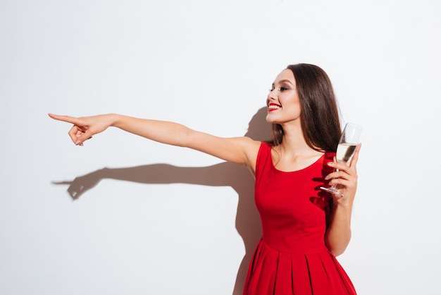 Smiling charming young woman in red dress drinking champagne and pointing away over white background