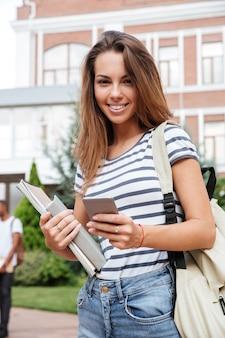 本を保持し、屋外でスマートフォンを使用してバックパックで魅力的な若い女性の学生を笑顔