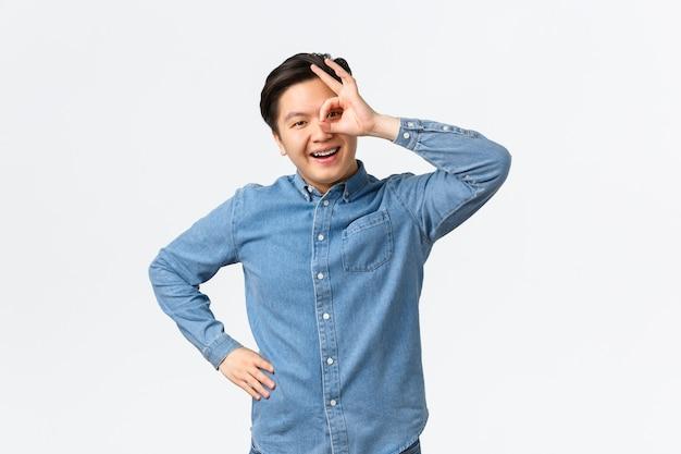 웃고 있는 명랑하고 만족스러운 아시아 남성은 눈 위에 괜찮은 제스처를 보여주고, 만족스러운 표정으로 훑어보고, 모든 것이 좋은 것을 확인하고, 우수한 서비스를 추천하고, 보증합니다.
