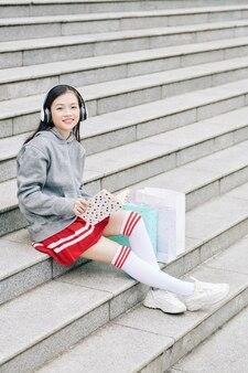 Улыбающаяся веселая азиатская девушка отдыхает на ступенях после покупок, чтения книги и прослушивания музыки