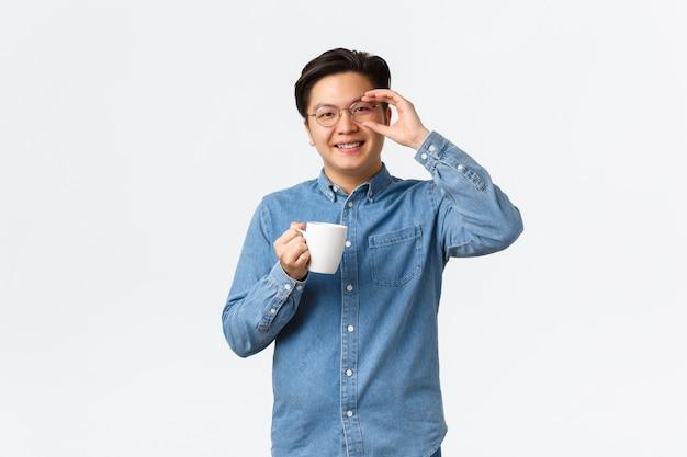 Улыбающийся веселый азиатский парень, офисный работник в очках, перерыв на обед, стоя с чашкой кофе на белом фоне. мужчина пьет из кружки и выглядит оптимистично, утренняя рутина.