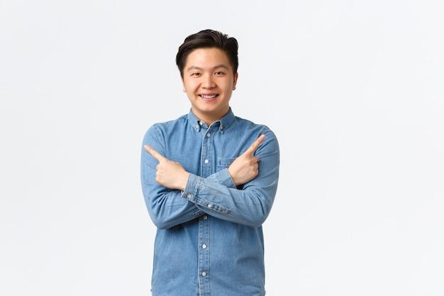 中かっこで笑顔の陽気なアジア人男性が発表します。男は左右のバリエーションで指を横向きにし、いくつかのオプションを示し、店をお勧めし、白い背景に立っています
