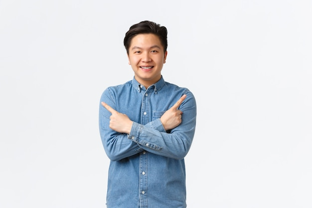 Smiling cheerful asian man with braces making announcement. guy pointing fingers sideways at left and right variants, showing few options, recommend stores, standing white background