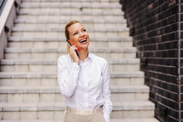 屋外に立って電話で話している陽気な魅力的な金髪のファッショナブルな女性の笑顔。
