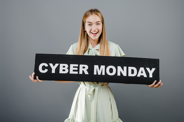 Smiling cheerful blonde girl with cyber monday sign isolated over grey