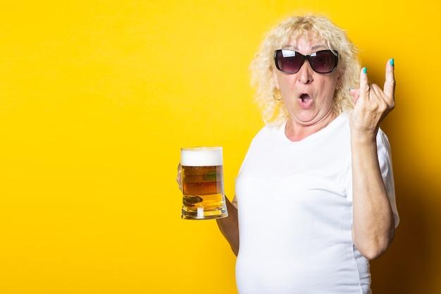 맥주 한 잔을 들고 로커 염소를 보여주는 밝은 금발 늙은 여자 미소