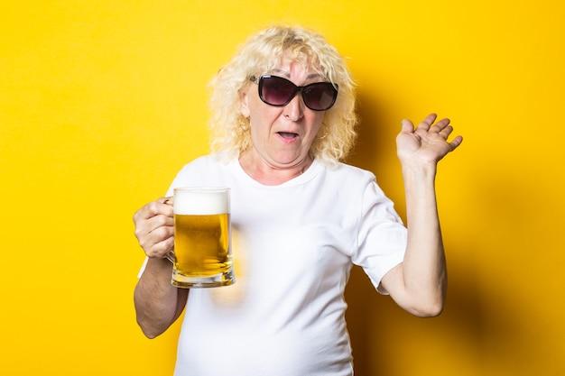흰색 티셔츠에 웃는 쾌활한 금발 늙은 여자는 맥주 한 잔을 보유하고 그녀의 손을 파도