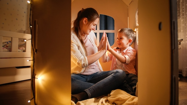 Smiling cheerful boy playing patty cake with young mother in toy small house at night. concept of child playing and family having time together at night.