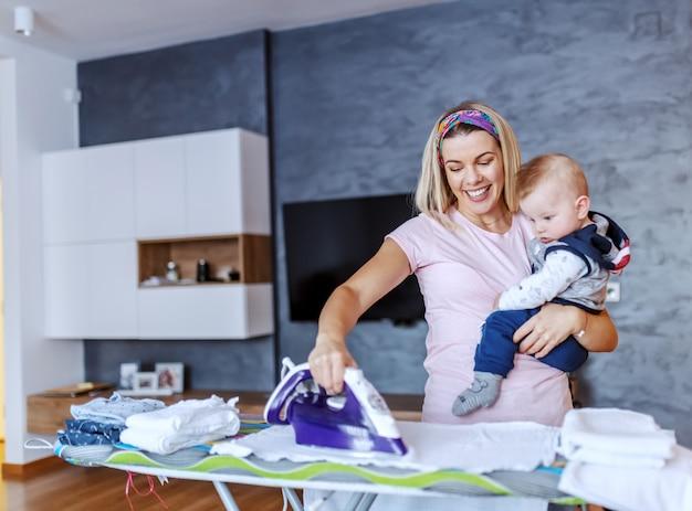 陽気な白人金髪の若い主婦がリビングルームに立って、彼女の男の子を押しながら洗濯物にアイロンをかけて笑っています。