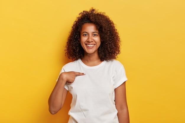 La ragazza sorridente allegra dalla pelle scura indica se stessa, mostra lo spazio del mockup su una maglietta bianca, felice di essere scelta, modelli contro il muro giallo. la giovane donna afro e spensierata mi chiede chi sono
