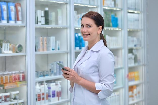 다른 의료 제품이 있는 선반 사이에서 카메라를 위해 포즈를 취한 손에 휴대폰을 들고 웃고 있는 쾌활한 약사