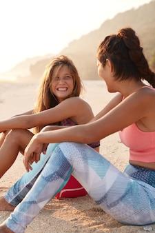 笑顔の陽気なヨーロッパの女性は彼女の女性の仲間を前向きに見ています
