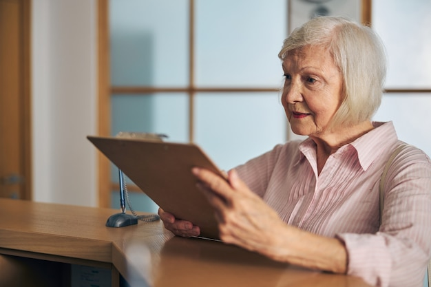 Улыбающаяся жизнерадостная женщина смотрит на прайс-лист в медицинской клинике, стоя возле стойки регистрации