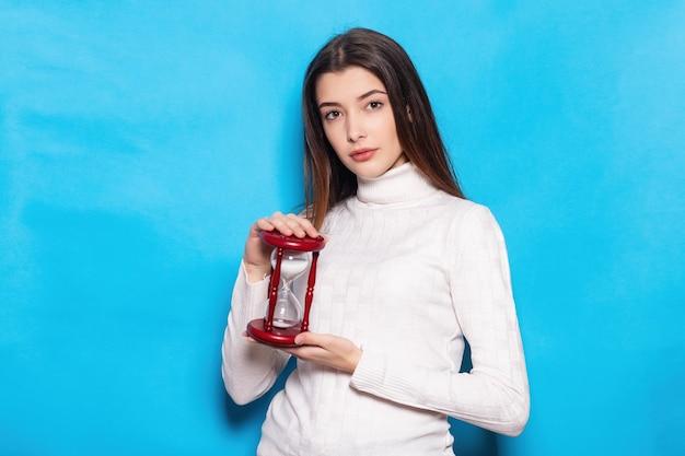 Улыбающаяся веселая забавная молодая брюнетка женщина 20-х годов в простом повседневном стоянии держится в руках, указывая указательным пальцем на песочные часы, изолированными на ярко-синем фоне стены студийный портрет