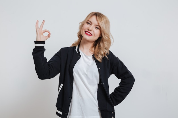 Smiling cheerful girl in casual clothes showing okay sign