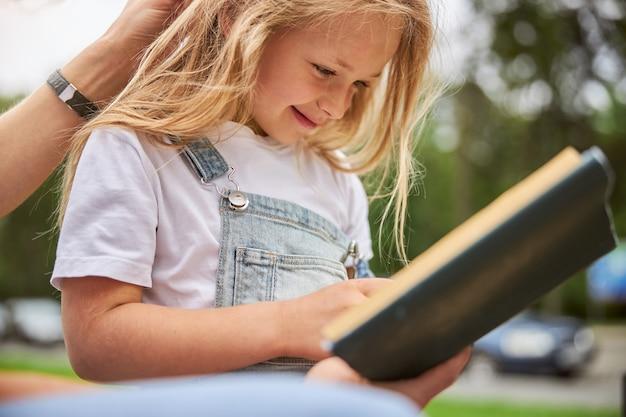 녹색 도시 공원에서 시간을 보내는 동안 동화를 읽고 웃는 명랑 소녀