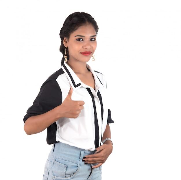 Усмехаясь жизнерадостная девушка показывая одобренный знак или большие пальцы руки вверх изолированные на пустом пространстве