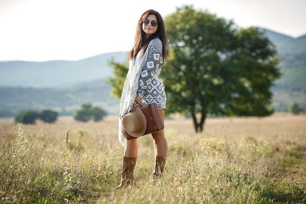 Улыбающаяся жизнерадостная девушка с кудрявыми волосами дышит полной грудью и наслаждается свободой, стоя на поле возле большого одинокого дерева.