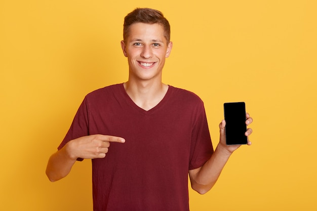 Smiling cheerful guy holding phone with blank screen