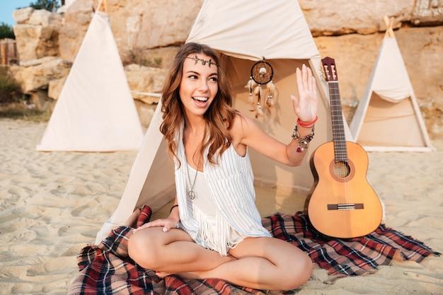 Улыбающаяся веселая девушка-хиппи приветствует кого-то, сидя в пляжной палатке