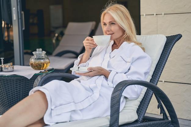 태양 침대에 앉아있는 동안 차 한잔 마시는 흰 목욕 가운에 쾌활한 아가씨 미소