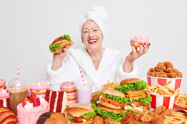 Smiling cheerful old woman feels very happy holds delicious hamburger and doughnut wearrs bathrobe and towel on head eats junk food