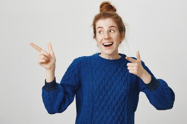 Улыбающаяся веселая рыжая девушка показывает рекламу, указывая влево