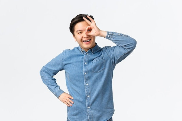 Smiling cheerful and satisfied asian man showing okay gesture over eye, looking through with pleased expression, assure everything good, recommend excellent service, guarantee.