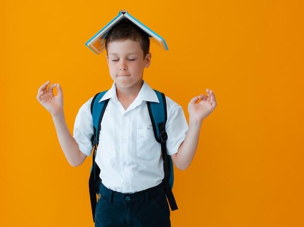 Улыбающийся веселый школьник на желтом фоне. ребенок с рюкзаком, книгами и тетрадями. мальчик готов учиться. обратно в школу.