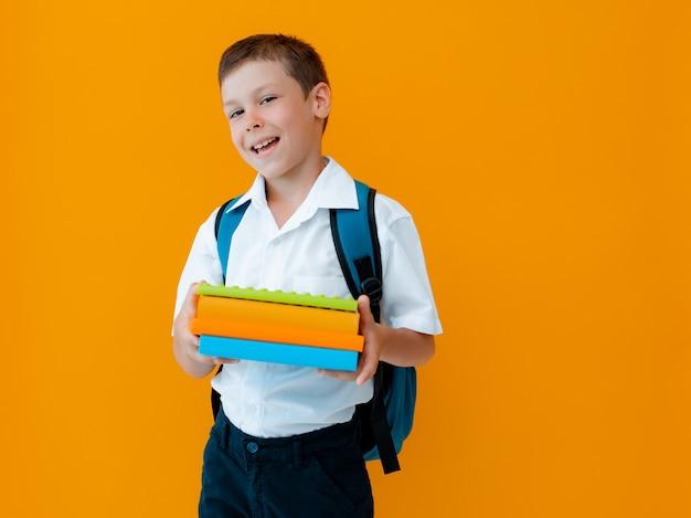 노란색 배경에 웃는 쾌활한 모범생. 배낭, 책, 공책을 든 아이.