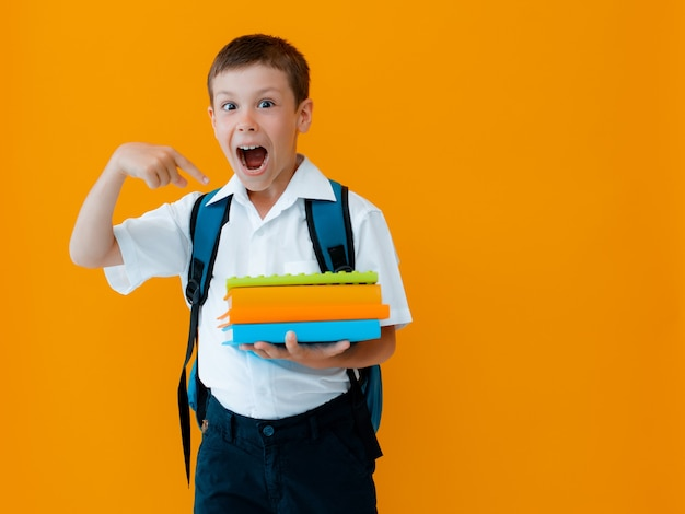 Улыбающийся веселый школьник на желтом фоне. ребенок с рюкзаком-сюрпризом, указывая жестом. мальчик в белой рубашке и школьной форме готов к учебе. обратно в школу.